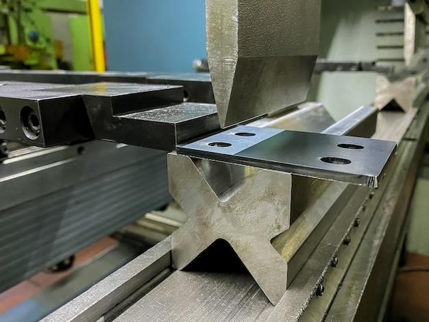 Bending of sheet metal parts using a sheet metal bending machine in factory