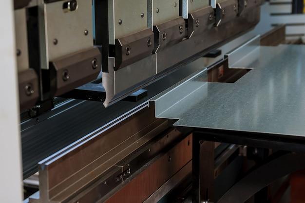 Гибка листового металла на гидравлическом гибочном станке на заводе.
