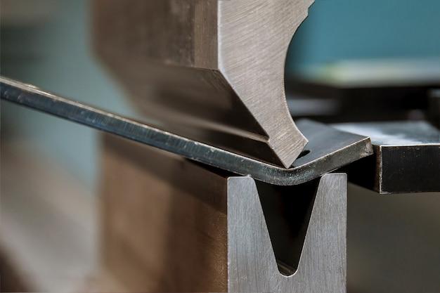 Гибка листового металла на гидравлическом станке на заводе. крупный план.