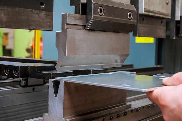Bending sheet metal with a hydraulic bending machine at the factory.