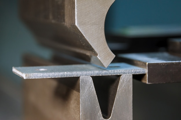 Bending sheet metal with a hydraulic machine at the factory closeup