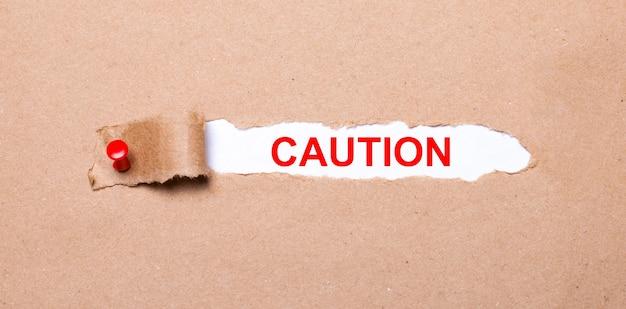 赤いボタンが付いたクラフト紙の破れたストリップの下には、注意というラベルの付いた白い紙があります。