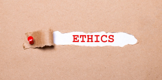 赤いボタンが付いたクラフト紙の破れたストリップの下には、ethicsというラベルの付いた白い紙があります。