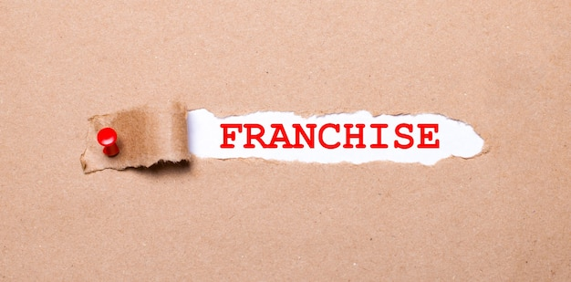 Под оторванной полосой крафт-бумаги, прикрепленной красной кнопкой, находится белая бумага с надписью franchise.