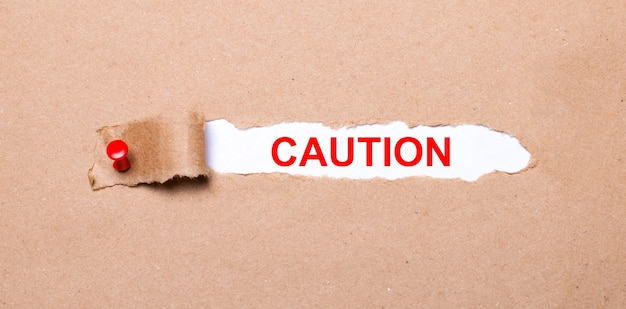 Beneath the torn strip of kraft paper attached with a red button is a white paper labeled caution.