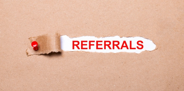 Beneath the torn strip of kraft paper attached with a red button is a white paper referrals