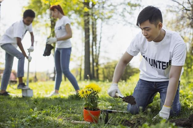 원예의 이점. 정원 도구를 사용하는 동안 무릎에 아시아 남성 자원 봉사 서
