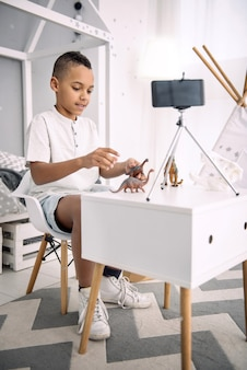 Benefits from visualization. enthusiastic afro american boy blogger playing with dinosaurs toys while recording video