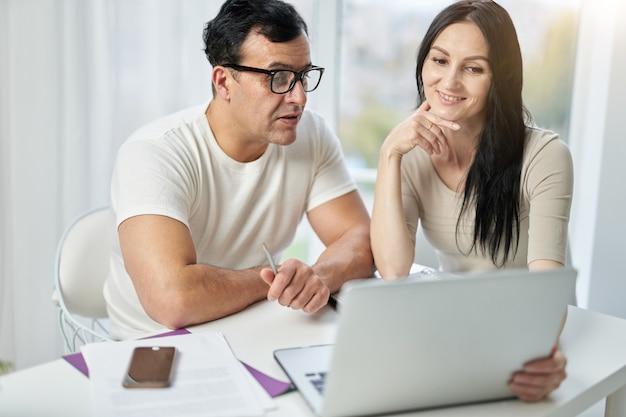 온라인 과정의 장점. 행복한 히스패닉 커플, 남성과 여성이 영상 통화를 하고, 원격으로 클라이언트와 연락하면서 웹캠으로 이야기하고, 집에서 노트북을 사용합니다.