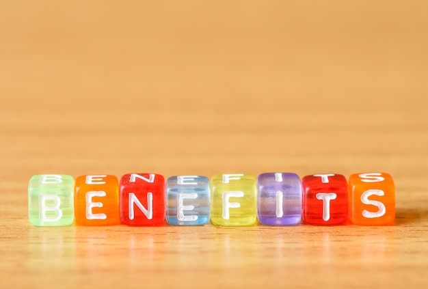 Benefits word made from different colors building block on table background