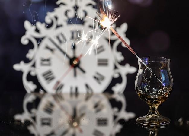 Бенгальская свеча в стакане на фоне часов.