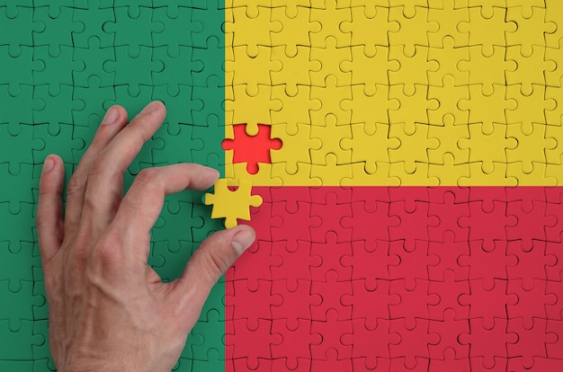 Benin flag  is depicted on a puzzle, which the man's hand completes to fold