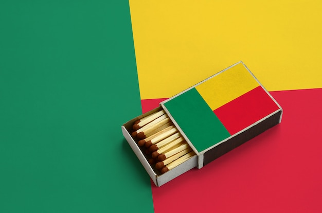 Benin flag  is shown in an open matchbox, which is filled with matches and lies on a large flag
