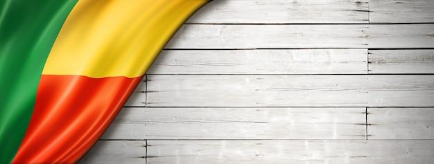 Флаг бенина на старой белой стене. горизонтальный панорамный баннер.