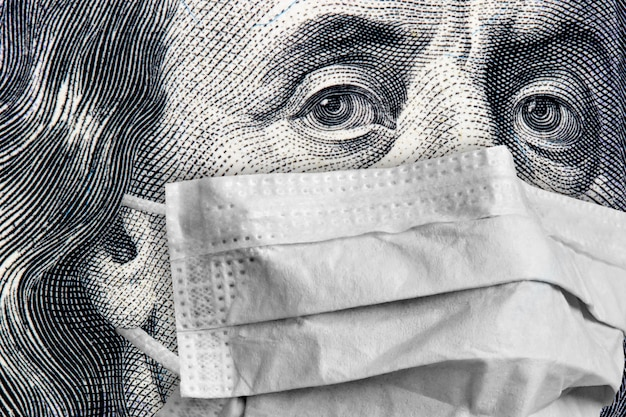 Benjamin franklin portrait close-up on 100 dollars banknote in a medical mask