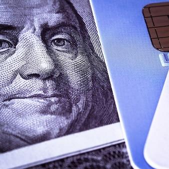Лицо бенджамина франклина на стодолларовой купюре рядом с кредитной картой. крупным планом.