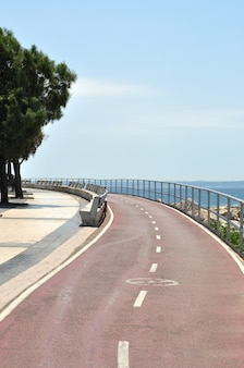 Bent of empty bicycle lane along seashore in sunny summer day