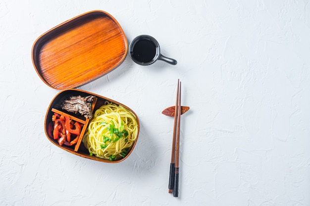 Bento beef noodles lunch box top view space for text on white table.
