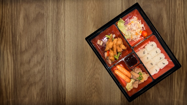 Bento set of pork chicken and sauces tempura japanese food on wood table restaurant.