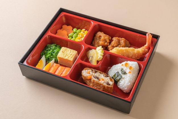 Bento set with rice ball, shrimps, sushi and vegetables