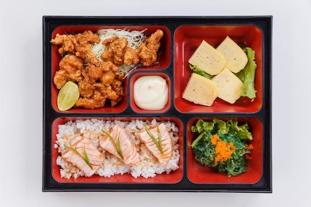 Жареный лосось bento с японской жареной курицей.