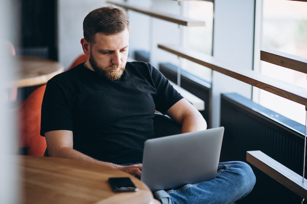 Beraded man working on laptop in a cafe