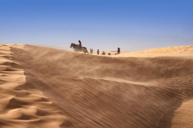 強風の砂嵐の間、ベルベル人はサハラ砂漠で馬に乗る
