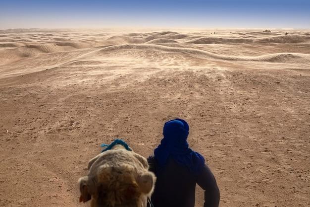 ベルベル人はラクダを背負って立ち、サハラ砂漠の遠くを見つめます