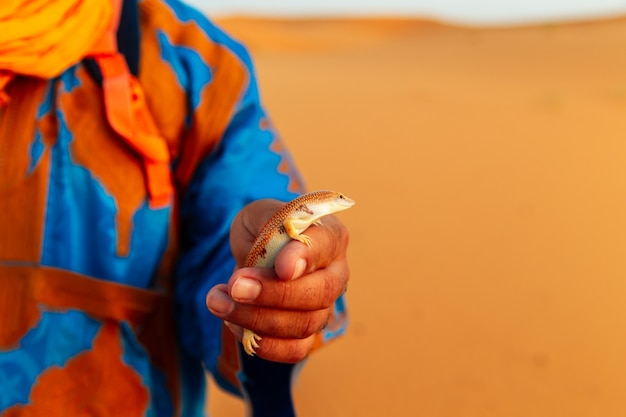 Berber in traditional dress holds a salamander in his hand.
