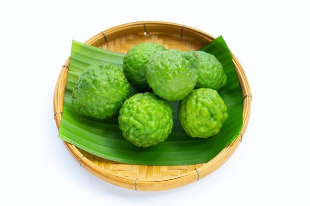 白い背景の上の竹かごのベルガモットカフィアライムハーブ新鮮な果物。