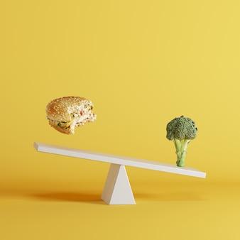黄色の背景に反対側の端に浮かぶbergerとブロッコリー野菜チップシーソー。