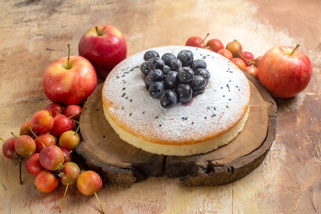 木の板にブドウと食欲をそそるケーキをベリーリンゴとベリー