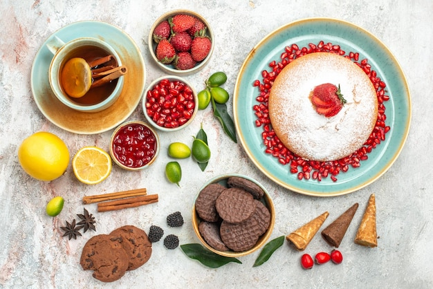 Ягоды и чай варенье лимон корица чашка чая пирожное с ягодами печенье