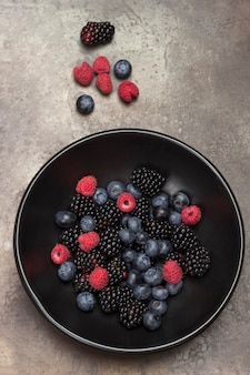 Berries in black ceramic plate: blackberry, cherry, blueberry and raspberry. gray surface. weight loss concept. flat lay