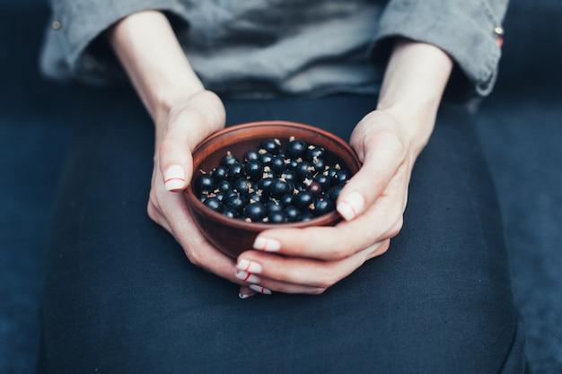 Berries of black currant in plates in female hands. vitamins and healthy eating concept