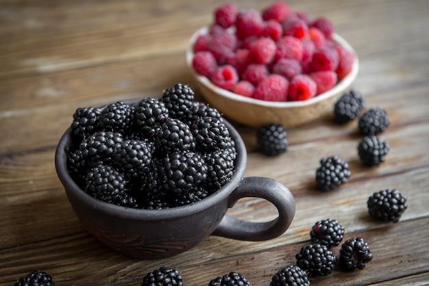 딸기 블랙 베리와 라스베리와 세라믹 접시가 테이블 위에 서 있습니다.