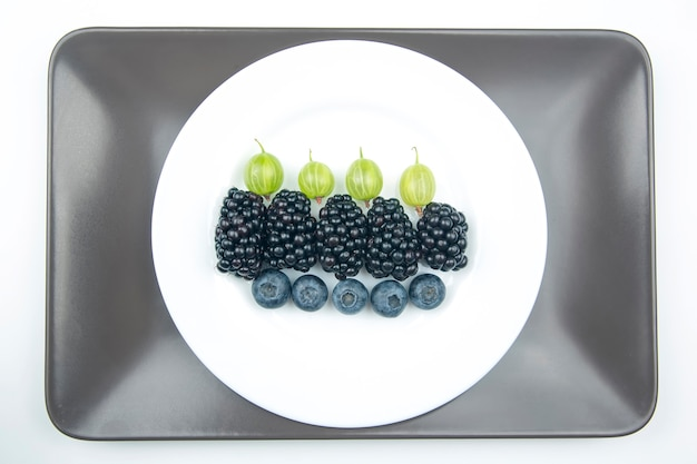 Berries blueberries, gooseberries and blackberries on white plate.