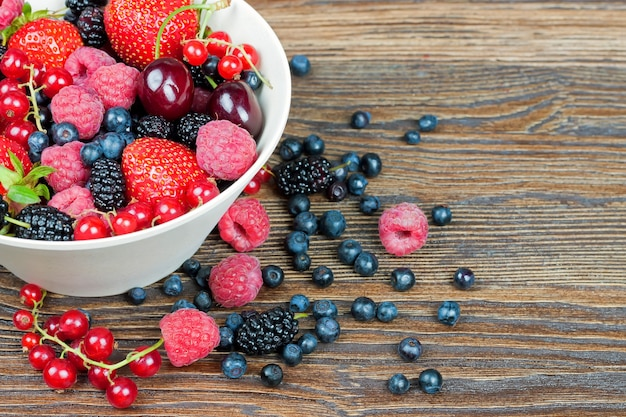 Berries in a bowl in the assortment on a brown wooden table