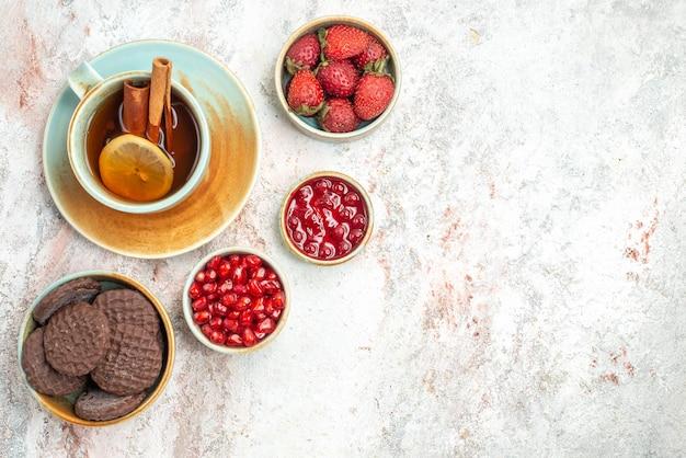Berries in bowls a cup of black tea with lemon bowls of berries jam cookies