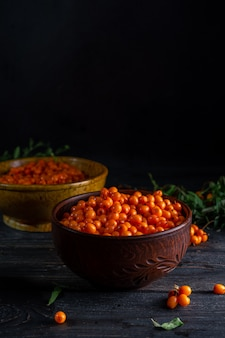 Berries and branches of sea buckthorn, bowls with berries on a dark wooden background