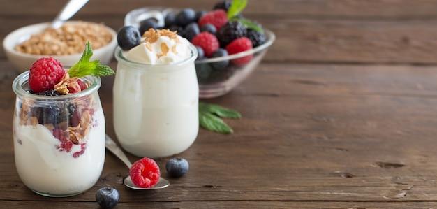 Ягоды, хлопья и свежий греческий йогурт на деревянном столе