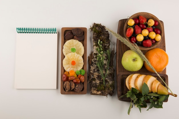 Berries, fruit mix and herbs in a wooden platter with a notebook aside