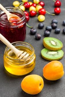 Ягоды, фрукты, мед, варенье на черном фоне