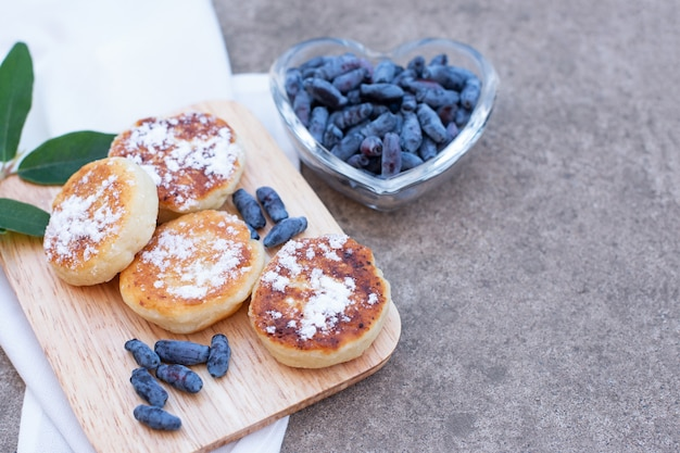 Berries of honeysuckle and pancakes on a concrete surface