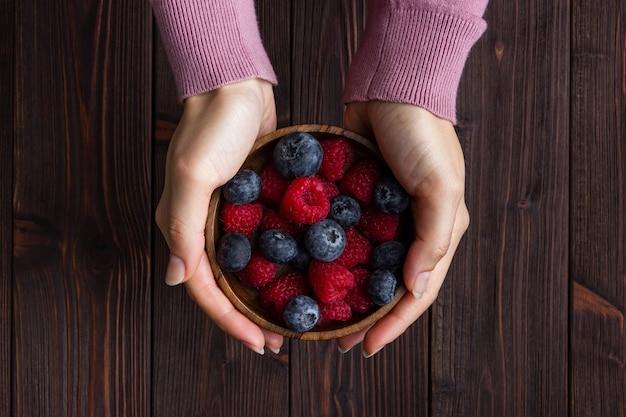 Ягоды в деревянной миске с женской рукой на деревянном столе. вид сверху свежей черники, малины.