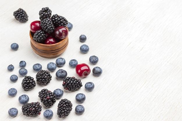 木製の箱とテーブルの上の果実:ブラックベリー、チェリー、ブルーベリー、ラズベリー。白い表面。上面図。コピースペース