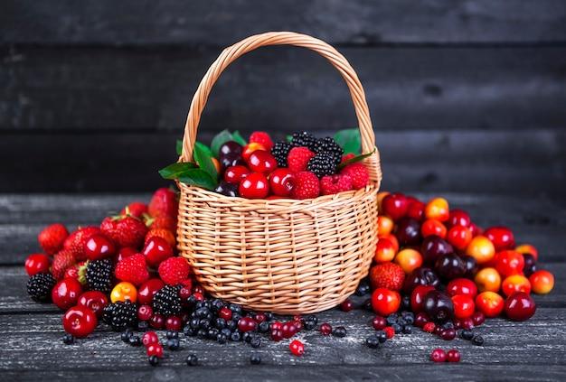 Berries mix in basket on dark wooden background