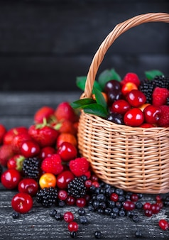 Berries mix in basket on dark wooden