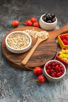 Berries oatmeal spoon on the cutting board colorful berries candies