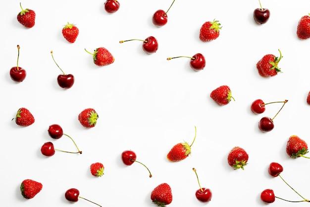 熟したイチゴとチェリーのベリーは、コピースペースのある白いテーブルの上に散らばっています。上面図。
